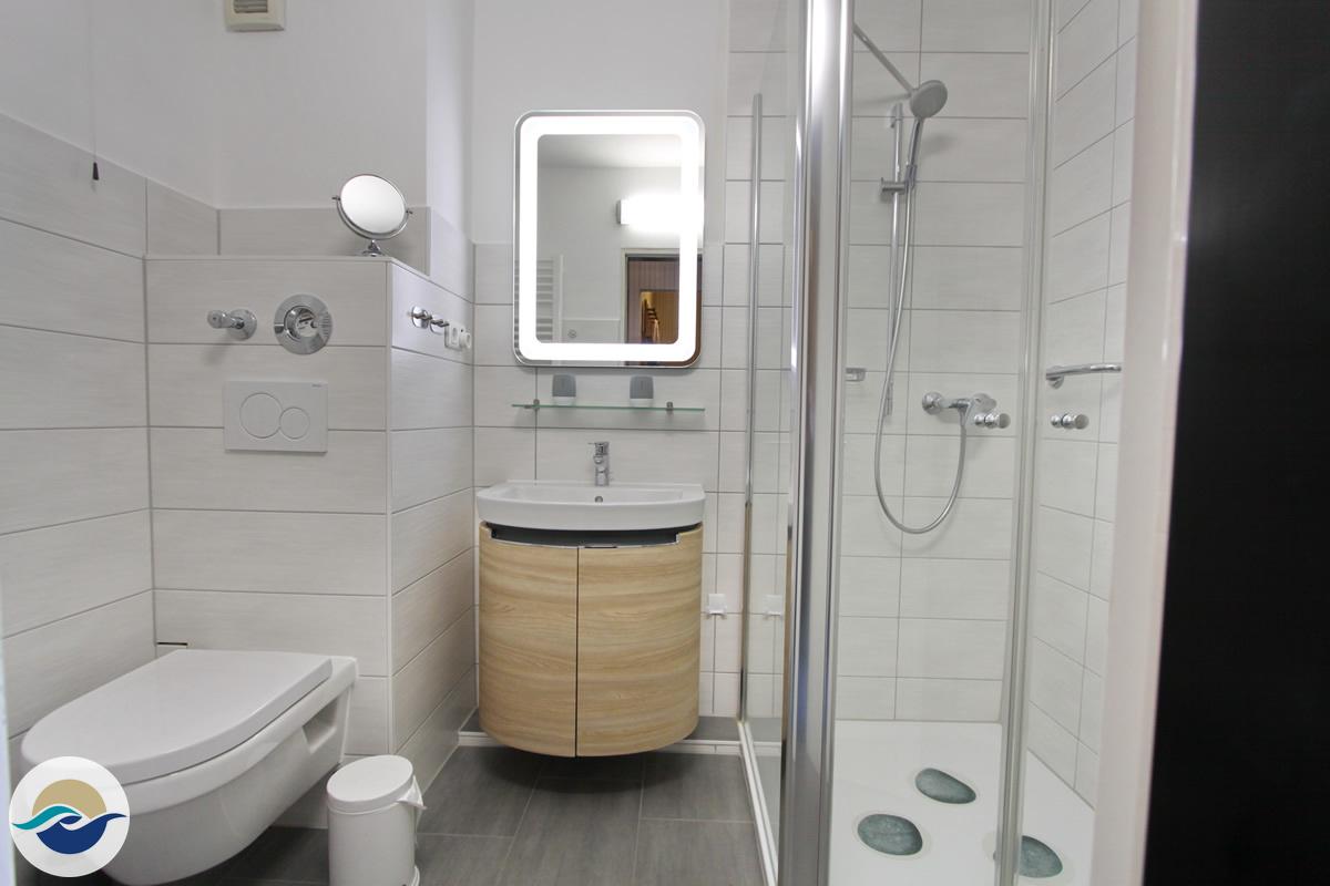 Ein modernes Badezimmer ist mit einem Handtuchheizkörper, einem Waschtisch mit Stauraum für Ihre Kosmetika und Spiegelschrank ausgestattet.