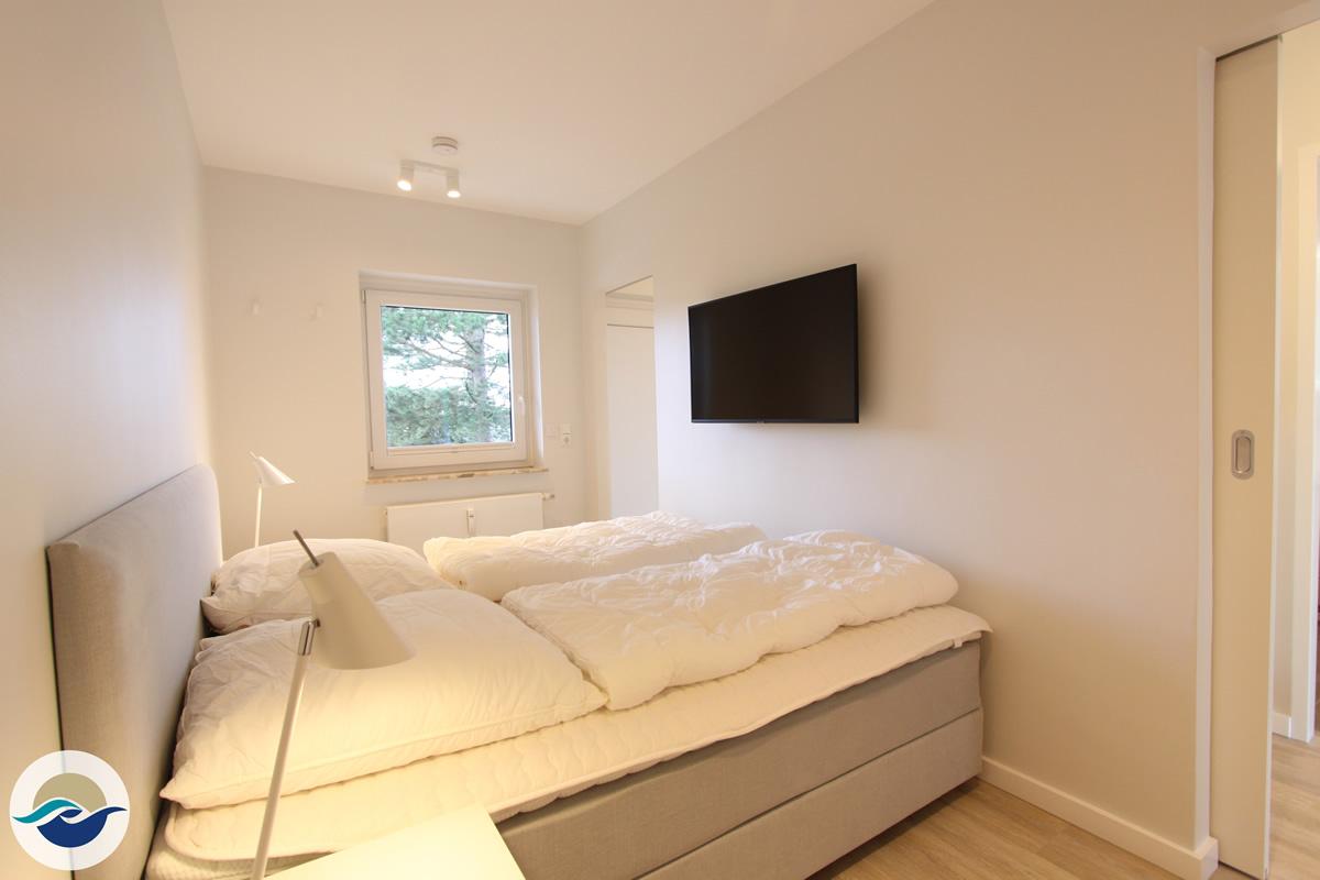 Das Schlafzimmer ist mit einem Boxspringbett (180 x 200 cm), einem Kleiderschrank und einem wandhängenden TV ausgestattet.