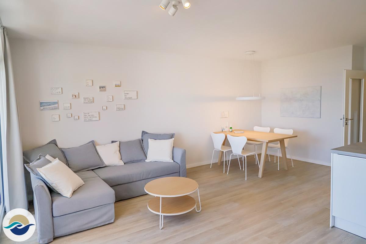 Das großzügige Wohnzimmer verfügt über eine Schlafcouch mit Sessel und einen Essbereich.